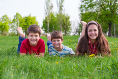 3 дет лежа совместно на луге зеленой травы Стоковые Фото