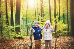 2 дет держа ветви в лесе осени Стоковые Изображения