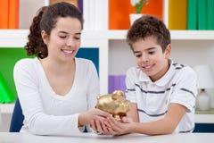 2 дет держа piggybank Стоковое Изображение