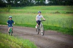 2 дет ехать на велосипедах на сельской дороге Стоковая Фотография