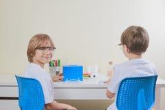 2 дет делая науку экспериментируют дома записывает старую принципиальной схемы изолированная образованием Стоковое Изображение RF