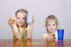 2 дет едят булочку на таблице Стоковое Фото