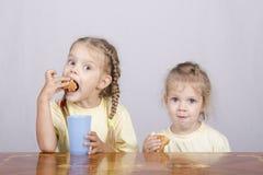2 дет едят булочку на таблице Стоковое Изображение