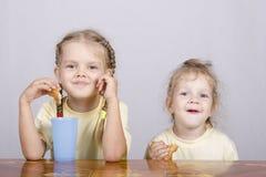 2 дет едят булочку на таблице Стоковая Фотография