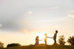 3 дет играют на заходе солнца Стоковое Изображение