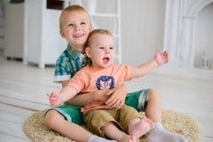2 дет играют пока сидящ на поле дома Стоковая Фотография