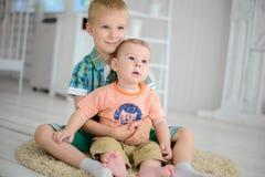 2 дет играют пока сидящ на поле дома Стоковое Изображение RF