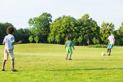 3 дет играют футбол Стоковая Фотография