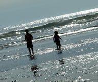 2 дет играя на пляже как Солнце сверкают на Wa Стоковое Изображение RF