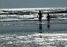 2 дет играя на пляже как Солнце сверкают на Wa Стоковые Фото
