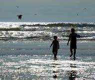 2 дет играя на пляже как Солнце сверкают на Wa Стоковое фото RF