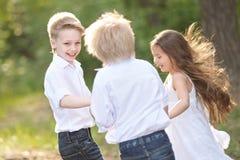3 дет играя на луге Стоковое фото RF