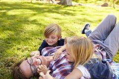 2 дет играя при их папа, лежа в парке, взгляд со стороны Стоковые Фотографии RF