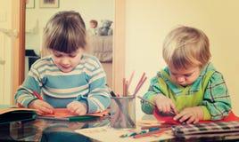 2 дет играя с бумагой и карандашами Стоковые Изображения