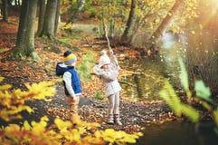 2 дет играя с ветвью около пруда Стоковое Фото