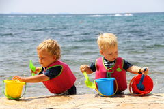 2 дет играя с водой в ведерках и лопаткоулавливателях морем Стоковые Фотографии RF