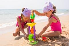 2 дет играя с игрушками в песке на пляже моря Стоковые Изображения