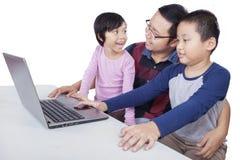 2 дет изучая с компьтер-книжкой и их учителем Стоковое Изображение