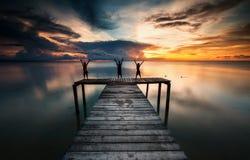 3 дет имея потеху на деревянной моле во время солнца установленного вниз Стоковое Изображение RF