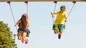2 дет имея потеху на swingset Стоковое Изображение
