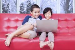 2 дет используя компьтер-книжку на софе Стоковая Фотография RF