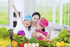 2 дет и их мать варя овощи Стоковые Изображения