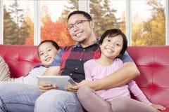 2 дет и их отец при таблетка сидя на софе Стоковое Изображение