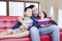 2 дет и их папа прочитали книгу Стоковая Фотография RF