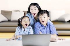 2 дет и мать сотрясенные с компьтер-книжкой Стоковое Изображение