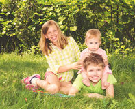 2 дет и ребёнок играя совместно на траве Группа в составе протокол доступа к хост-машине Стоковое фото RF
