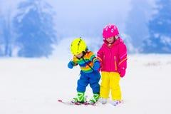 2 дет катаясь на лыжах в снежных горах Стоковое Изображение RF