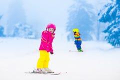 2 дет катаясь на лыжах в снежных горах Стоковые Фотографии RF