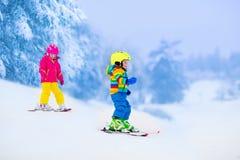2 дет катаясь на лыжах в снежных горах Стоковые Фото