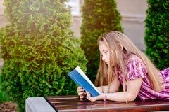 10 лет книги чтения девушки старого голубого глаза белокурой Стоковое фото RF