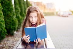 10 лет книги чтения девушки старого голубого глаза белокурой Стоковые Изображения