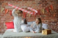 2 дет клали вверх жизнерадостный бой на большую кровать Стоковое Изображение