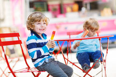 2 дет - мальчики отпрыска есть красочное мороженое в лете Стоковое Фото