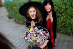 2 дет, мальчик и девушка, в черных костюмах для конфет взятия хеллоуина Стоковая Фотография