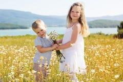 2 дет мальчик и девушка на поле стоцвета Стоковая Фотография