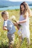 2 дет мальчик и девушка на поле стоцвета Стоковые Фотографии RF