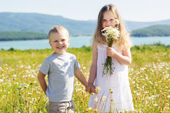 2 дет мальчик и девушка на поле стоцвета Стоковое фото RF