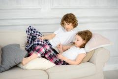 2 дет, мальчик и девушка, ложь на софе с таблеткой в руках Стоковая Фотография RF