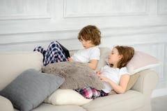 2 дет, мальчик и девушка, ложь на софе с таблеткой в руках Стоковая Фотография