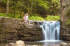 2 дет мальчик и девушка сидя около водопада в лесе Стоковые Фото