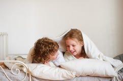 2 дет, мальчик и девушка, squirmy лежать на кровати в спальне Стоковая Фотография