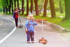 2 дет мальчик и самокаты катания девушки в городе Стоковое Фото