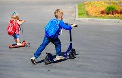 2 дет мальчик и самокаты катания девушки Стоковое Изображение