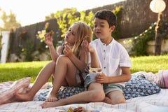 2 дет наслаждаясь пикником на одеяле в саде Стоковые Изображения