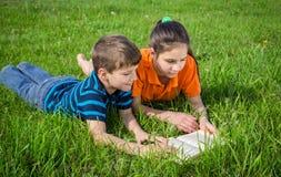 2 дет на зеленом луге с книгой Стоковое Изображение RF