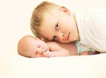 2 дет на кровати, самом старом брате обнимая самого молодого младенца Стоковые Фото